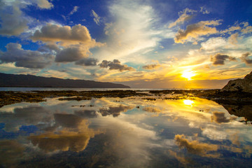 Beautiful Hawaiian sunset reflected in tide pool on the North Shore of Oahu