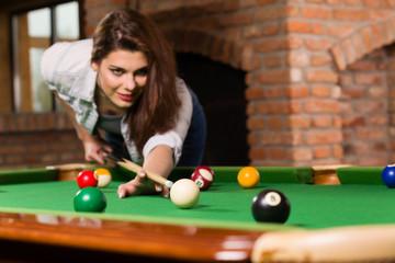 Woman playing billiards