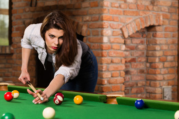 Woman playing billiards