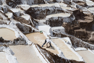 Worker collecting salt at The Maras salt ponds located at the Peru's Sacred Valley.