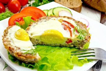 Tartlet meat with egg cut and vegetables on light board