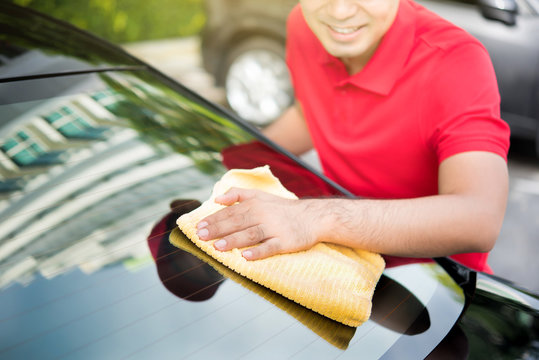 Auto service staff cleaning car rear windshield with microfiber