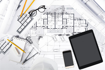 Construction plans with Tablet and drawing Tools on blueprints