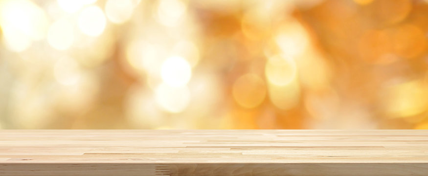 Wood table top on shiny gold bokeh abstract banner background