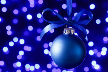 Blue christmas ball and blured purple lights at the background