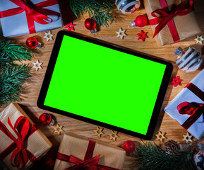 Tablet in Christmas wooden background with tree,gift and decorat