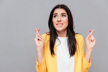 Confused young woman crossed fingers over grey background