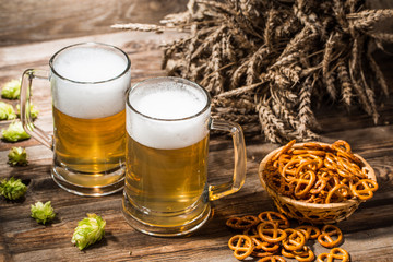 Beer in blackjack, hops, wheat spikes on table