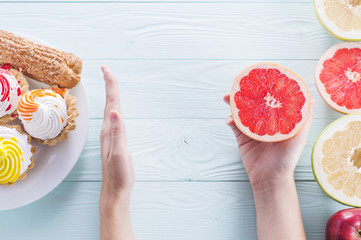 Hands of a young woman holding a grapefruit. Woman making a choice between sweets and fruits, made a choice in favor of fruits and holding half a grapefruit. Unhealthy vs healthy food, top view.