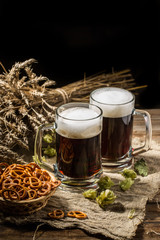 Couple beer mug with hop and pretzels on linen cloth