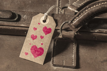 Tag with red hearts on old vintage suitcase. Concept of romantic travel, tourism and holiday destination.