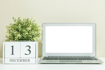White wooden calendar with black 13 december word with white blank space at center of computer notebook on white wood desk and cream wallpaper textured background , selective focus at the calendar