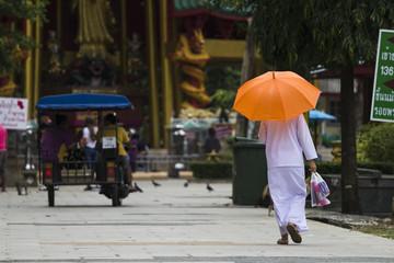 Buddhist with orange umbrella