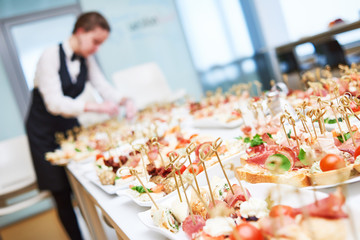 Catering. Restaurant waitress serving table with food