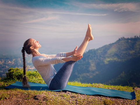 Woman doing Ashtanga Vinyasa Yoga asana Navasana - boat pose