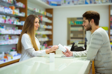 Attractive smiling pharmacist giving her client pills at the local pharmacy