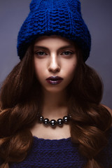 Beautiful girl in winter knitted hat blue color with a necklace around the neck of pearls. Young model with gentle makeup and silver lips. Warm winter picture. Beauty face.