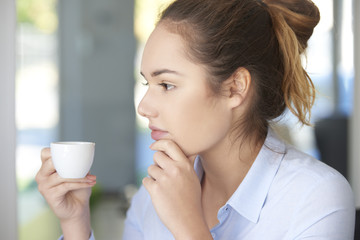 Coffee break in the office. Close-up shot of a thoughtful young assistant drinking a cup of coffee while sitting in the office.
