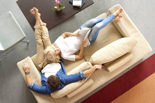 High angle view of a happy couple relaxing on cosy sofa at home. Beautiful blond woman reading a book while casual man using her digital tablet.