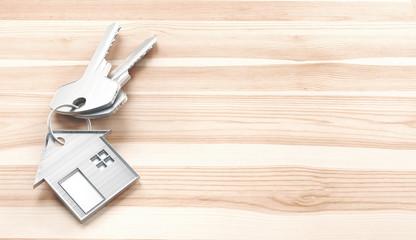 Chiavi di casa con portachiavi su tavolo legno