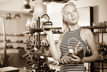 Cheerful young woman selecting from two pairs of shoes