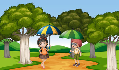 Two kids with umbrella in the park
