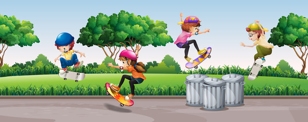 Four kids skateboarding in park