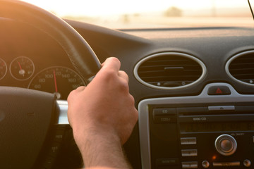A picture of someone's hand while they are driving