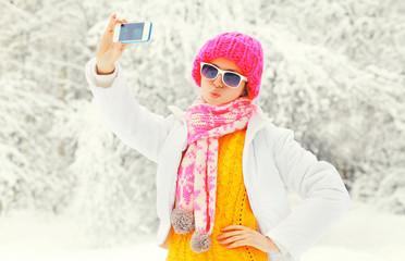 Fashion winter woman taking photo self portrait on smartphone ov