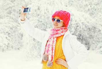 Fashion winter woman taking picture self portrait on smartphone