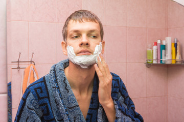 The young man gets shaving foam on his cheeks