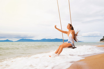 Young smiling woman on beach swing making selfie.  Vacation concept.