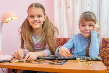 Two children are considered a collection of coins in albums
