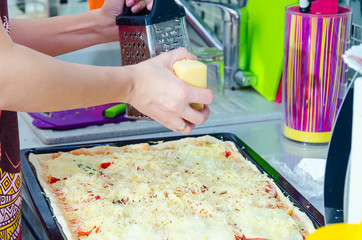 Woman hands grating cheese on the pizza. Young woman preparing the pizza in the kitchen.
