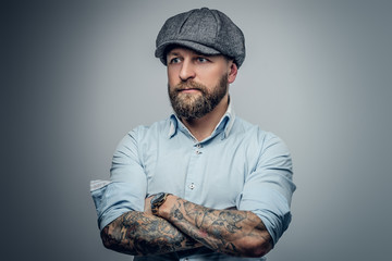 Bearded male in a shirt and tweed cap.