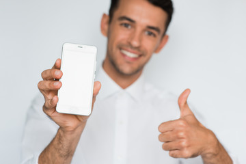 Portrait of young handsome man showing a blank smart phone screen with thumbs up isolated on a light gray background. Smile caucasian businessman with phone in studio.