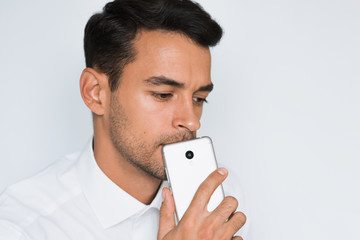 Portrait of handsome thinking serious man holding mobile phone with hand, put on chin, on gray background. Technology and connection idea. Young caucasian businessman look down in studio shooting.