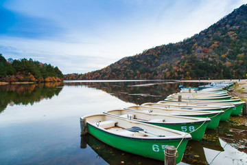 Fishing boat park on lake in evening autumn mountain