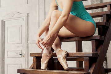 Young female ballet dancer tying ribbons on their Pointe. Closeup legs and shoes