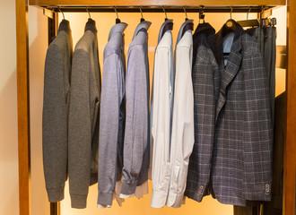 Menswear, men's wardrobe. Men's jackets on hangers