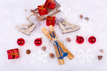 Xmas or new year composition with holiday decorations - little cristmas baubles on snow with toy skates, skis and gifts top on the sledge. Christmas card