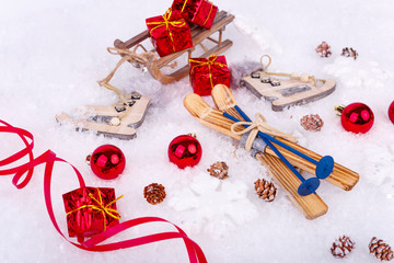 Xmas or new year composition with holiday decorations - little cristmas baubles, red satin ribbon on snow with toy skates, skis and gifts on the sledge. Christmas card