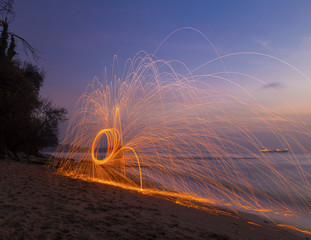 Man twirling fireworks on beach at sunrise