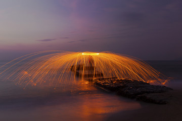 Man twirling fireworks on coastline at sunrise