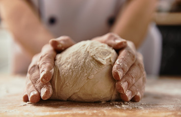 Close-up of chef hands kneading raw bread dough on wooden board.