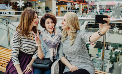 Three women girlfriend take a break in the New Year shopping in the mall and taking selfie at smartphone