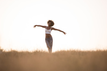 young black girl dances outdoors in a meadow