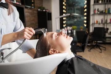 Beautician washing woman's head