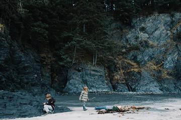 Three children exploring on beach