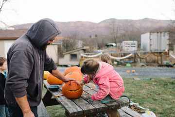 Father and children, outdoors, carving pumpkins
